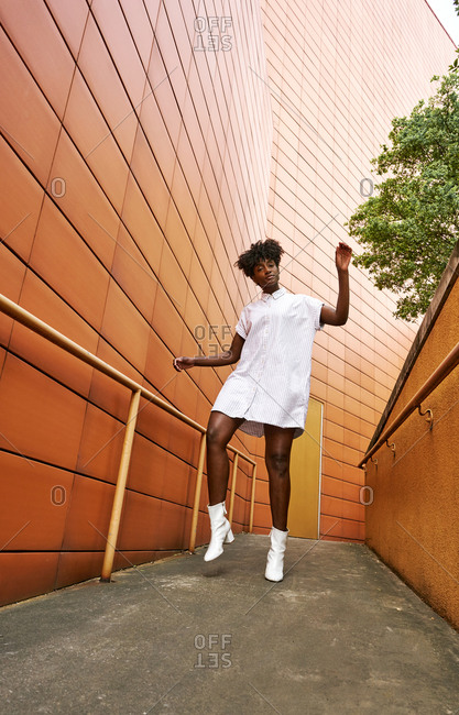 Young black female in trendy white dress and boots posing on street beside modern building with vivid orange exterior