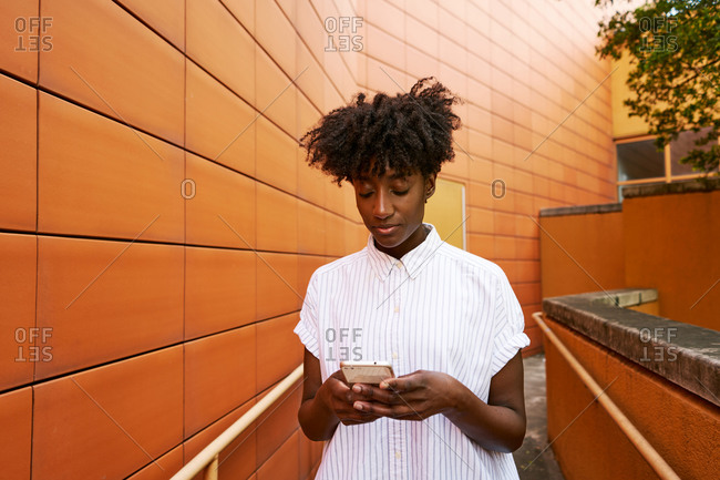 Adult African American female in white casual shirt messaging on smartphone standing on street against vibrant orange tiled facade of contemporary building in downtown