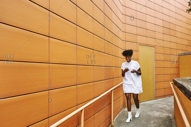 Cheerful Adult African American female in white casual shirt walking while messaging on smartphone on street against vibrant orange tiled facade of contemporary building in downtown