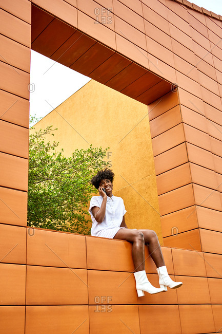 Low angle of young African American female in trendy white outfit smiling away and making phone call on street while sitting on wall contemporary building with bright orange and yellow walls