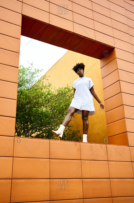From below full length cool relaxed African American female in stylish white dress and boots standing at square shaped wall of modern building with colorful facade
