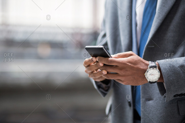 Faceless shot of black businessman in suit and watch using smartphone outside.