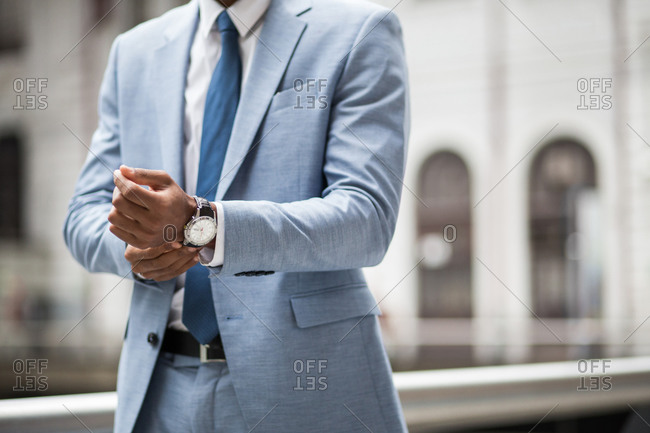 Faceless shot of black businessman in suit and watch outside