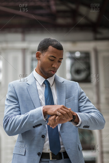 Handsome African-American man in suit looking at watch checking time standing outside.