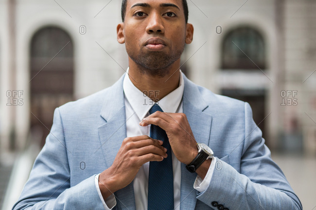 Close-up portrait of handsome serious African-American man in trendy blue suit rearranging tie