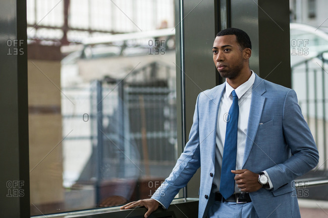 Young African-American man wearing elegant blue suit and standing looking away