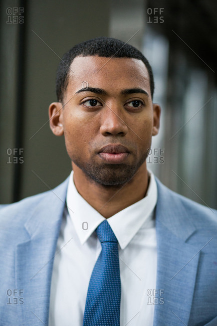 Close-up portrait of handsome serious African-American man in trendy blue suit and tie looking away pensively.