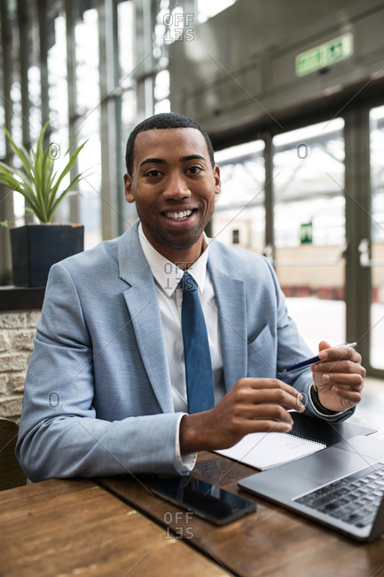 Young African-American man in blue suit sitting at wooden table