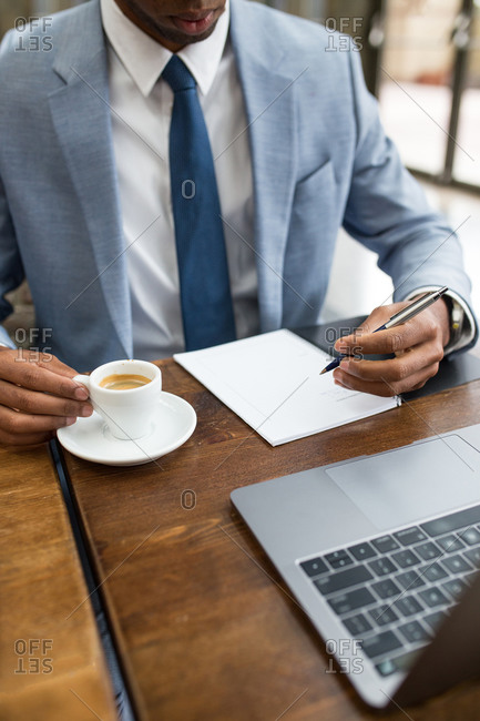Faceless businessman sitting at desk with cup of freshly brewed coffee and taking notes in pad with pen.