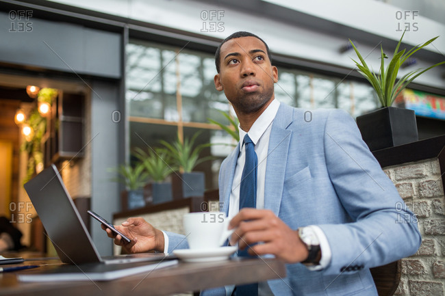 Black businessman sitting at desk with cup of freshly brewed coffee