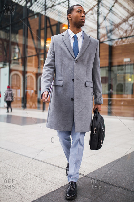 Handsome African-American man in trendy elegant suit and coat walking with suitcase and laptop in hands.