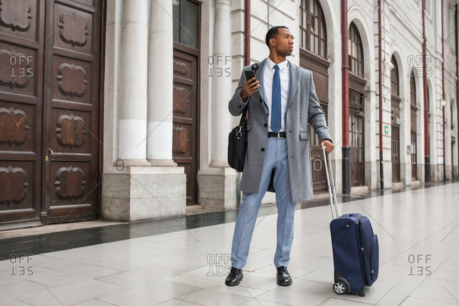 Handsome African-American businessman in trendy elegant suit and coat standing with suitcase