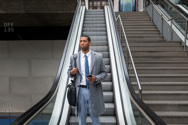 Handsome black businessman in coat and with phone walking down moving stairs while commuting.