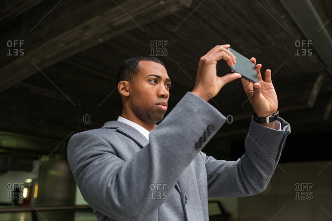 Back view of black man in suit using smartphone and taking photo of railway building from inside.
