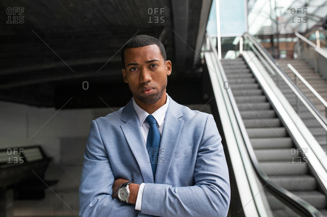 Close-up portrait of handsome serious African-American man in trendy blue suit and tie looking at camera pensively.