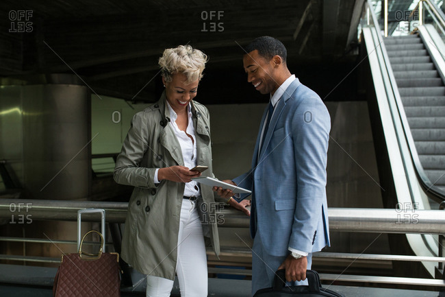 Cheerful elegant African-American man and woman watching tablet together and smiling.