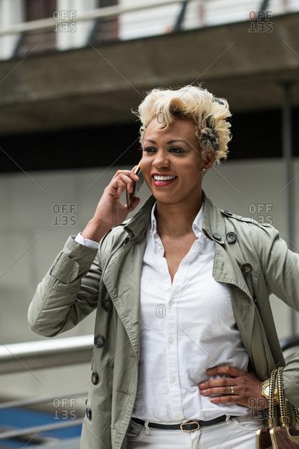 Cheerful African-American elegant woman in coat using phone