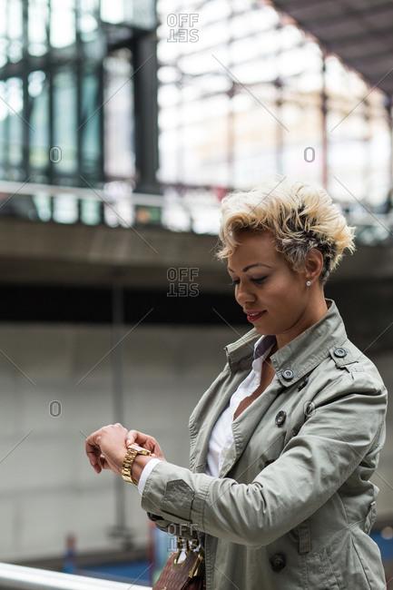 Cheerful African-American elegant woman checking watch