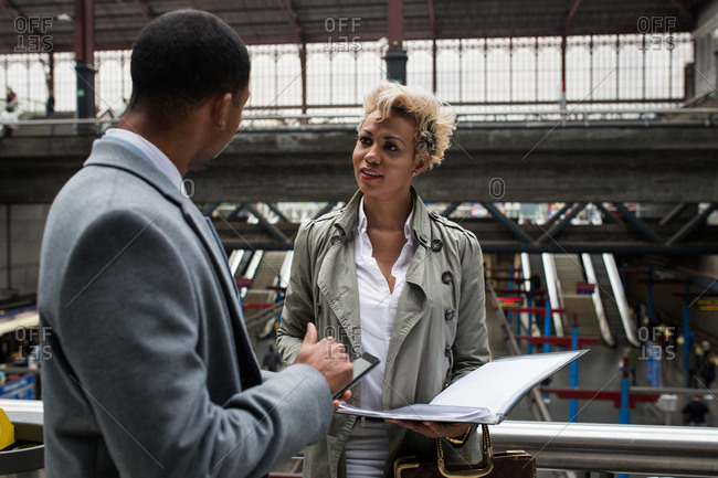 Beautiful African-American woman and man in elegant outfits discussing papers and news standing on station.
