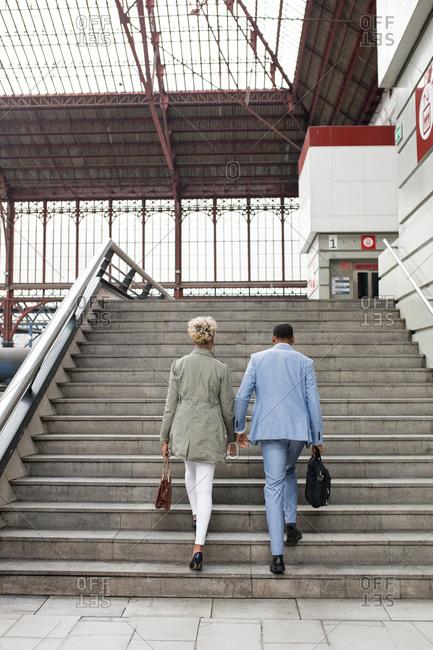 Elegant black woman and man having talk while walking down stairs on railway station.