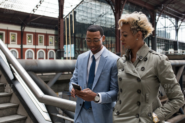 Laughing elegant man and woman with papers and smartphone standing on bridge of railway station and chatting.