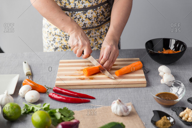 Woman cutting carrots on cutting board