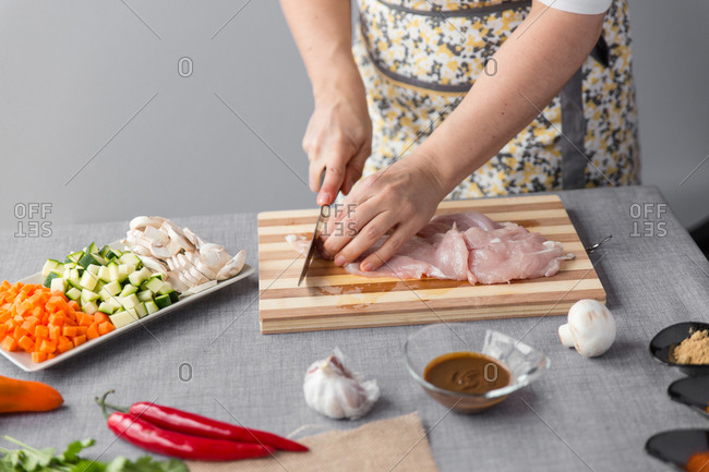 Woman cutting chicken on cutting board