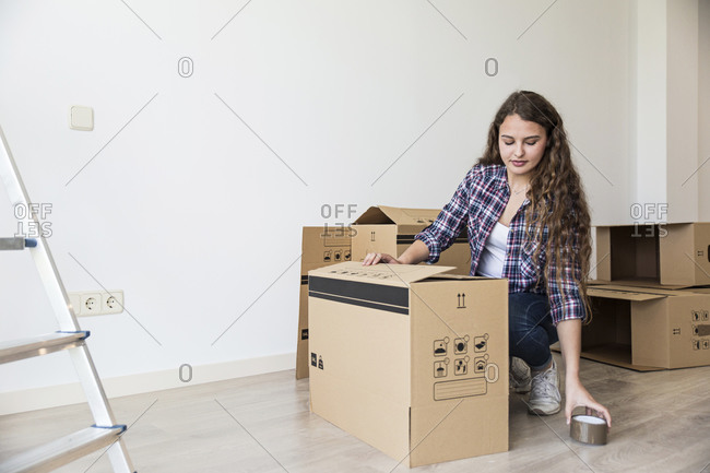 Cute female sitting near carton boxes and ladder using duct tape in empty apartment