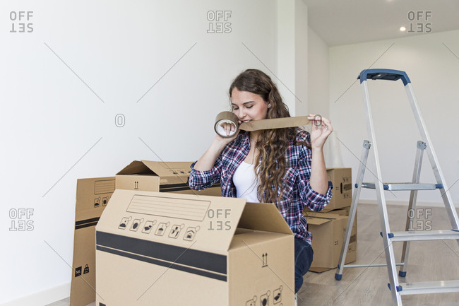 Cute female sitting near carton boxes and ladder cutting duct tape with teeth in empty apartment