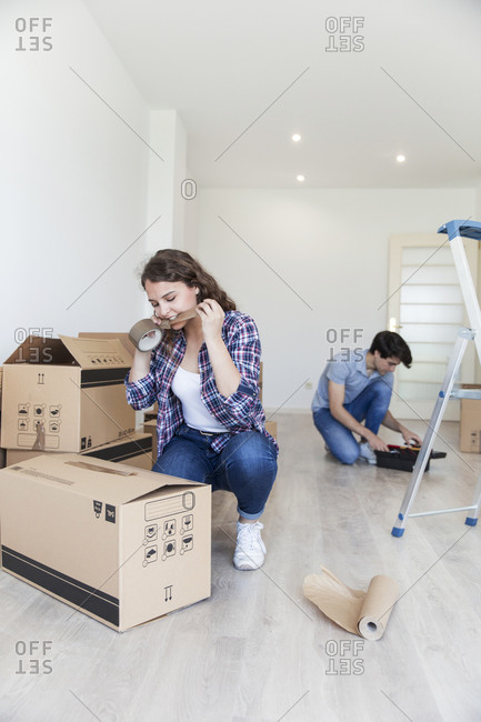 Young female cutting duct tape with teeth sitting near carton boxes and male sitting near black box in empty apartment