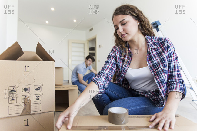 Young female using duct tape sitting near carton boxes and male sitting near black box in empty apartment
