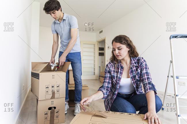 Young male and female in empty apartment opening carton boxes with ladder on floor
