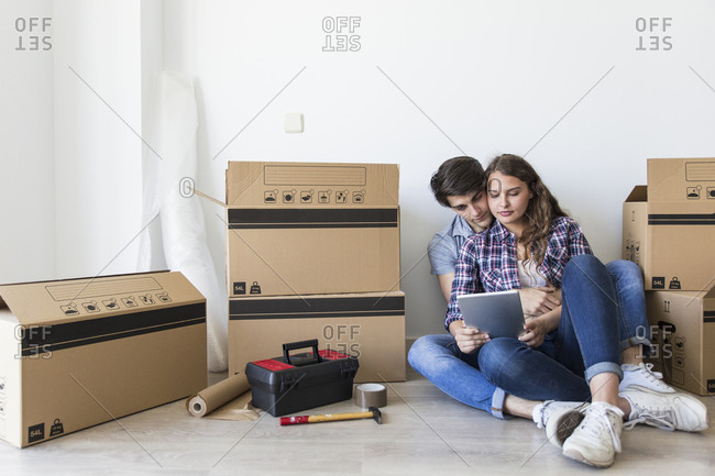 Young cute couple sitting with tablet and smiling on floor with carton boxes and tools in cozy apartment