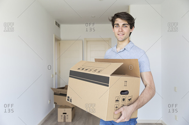 Handsome young male holding carton box in empty room looking at camera and smiling
