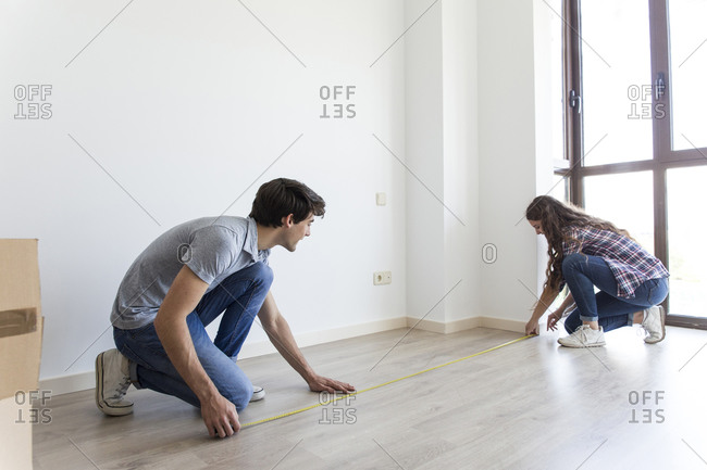 Young male and female measuring floor with linear tape in apartment with carton boxes