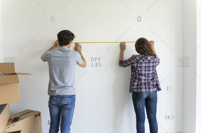 Young male and female measuring wall with linear tape in apartment with carton boxes