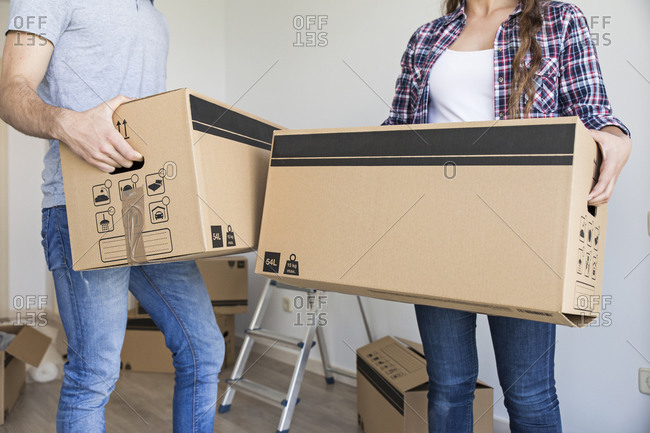 Young couple holding carton boxes in new apartment taking and smiling