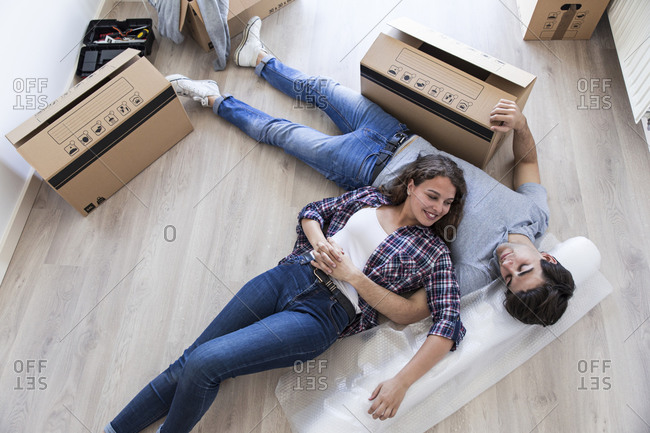 Young couple laying together on floor with carton boxes holding hands and looking at each other