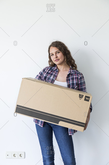 Young sweet female holding carton box in empty room looking at camera and smiling