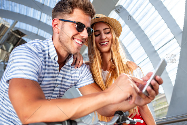 Handsome young man and pretty woman smiling and browsing modern smartphone while leaning on bicycle in roofed pathway on sunny day