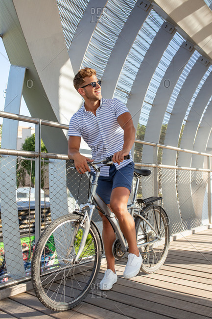 Young man while riding bicycle in roofed pathway on sunny day