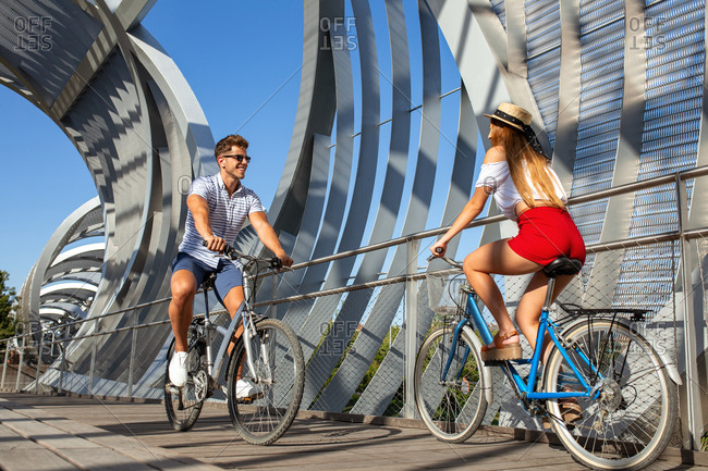 Young man and woman smiling and looking at camera while riding bicycles in roofed pathway on sunny day