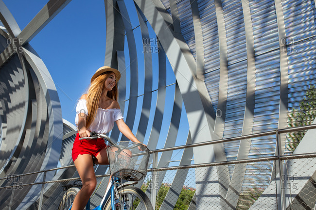 Young woman smiling while riding bicycle in roofed pathway on sunny day