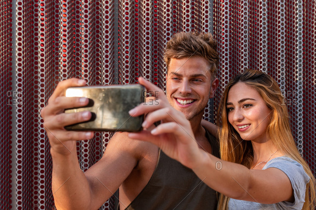 Attractive young man and woman smiling and posing for selfie while standing near wall on street