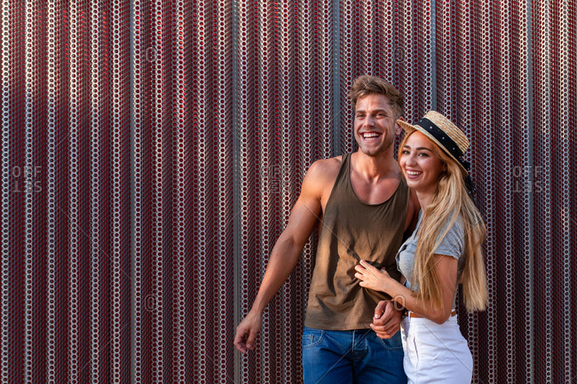 Handsome young man and pretty woman smiling and looking at each other while standing near metal wall on street and embracing