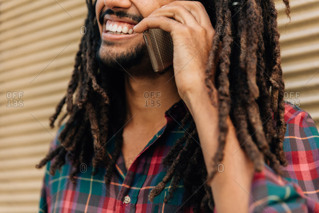 Man with dreadlocks talking on the phone