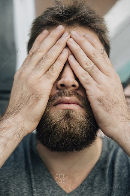 Bearded man covering his eyes