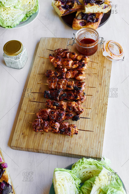 Cooked chicken skewers with spicy sticky glaze on wooden cutting board