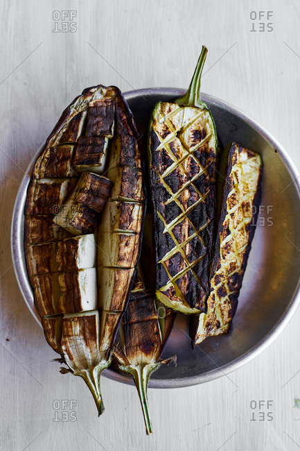 Grilled aubergines and zucchini halves on barbecue
