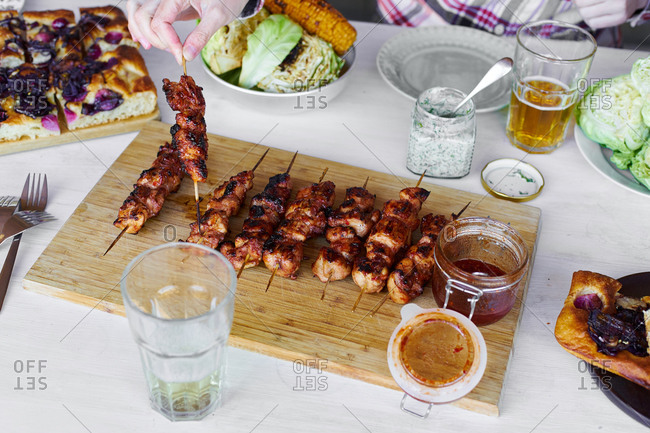 Family having a dinner on a terrace. Chicken skewers, roasted vegetables, focaccia and cider.